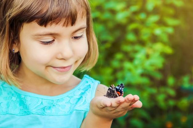 Kind met een vlinder. selectieve aandacht. natuur. Premium Foto