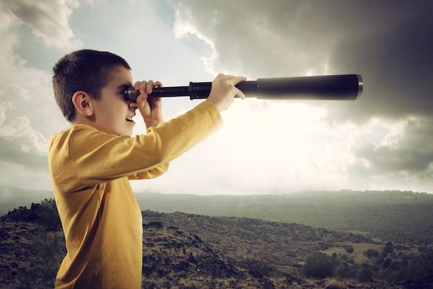 Kind met kijker zoekt ver naar een nieuw avontuur Premium Foto