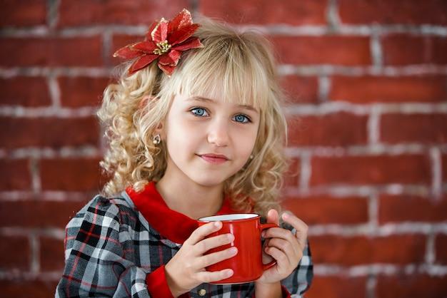 Kind met rode kop warme chocolademelk of chocolade met marshmallow. Premium Foto