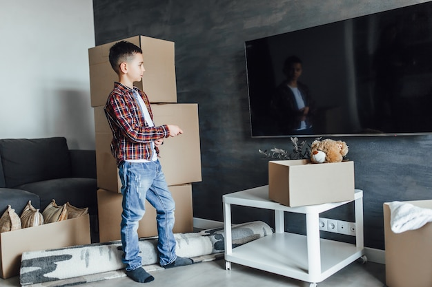 Kind naar een nieuw appartement, wachtend op films kijken met dozen uitpakken Premium Foto