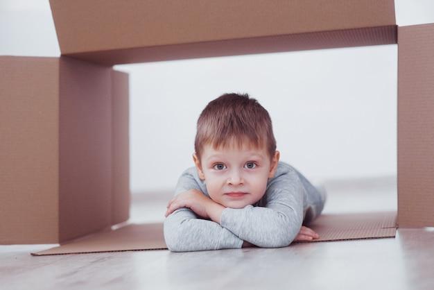 Kind peuter jongen spelen in kartonnen doos. jeugd, reparaties en nieuw huisconcept. Premium Foto