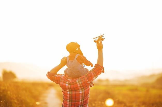 Kind proefvlieger met vliegtuigdromen van het reizen in de zomer in aard bij zonsondergang, Premium Foto
