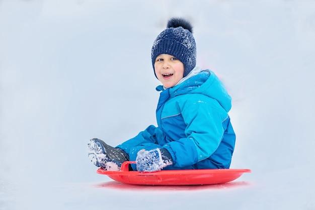 Kind rolt een sneeuwheuvel naar beneden. jongen die onderaan sneeuwheuvel glijdt in de winter. Premium Foto