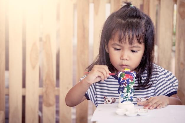 Kind schilderen, schattig klein meisje plezier samen op stucwerk pop te schilderen Premium Foto