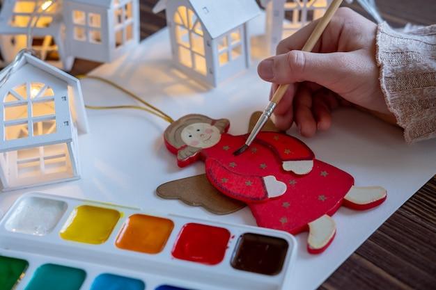 Kind schildert speelgoed, decoraties voor de kerstboom, creativiteit van kinderen, concept Premium Foto