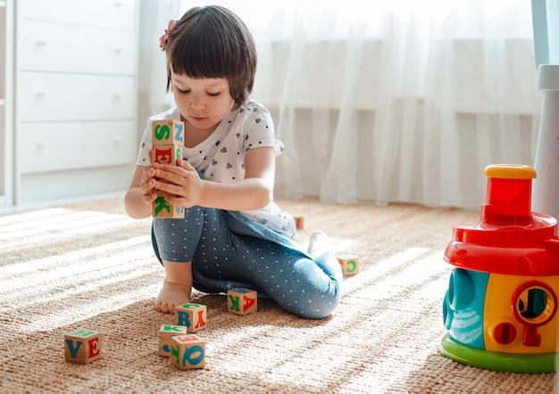 Kind speelt met houten blokken met letters op vloer kamer meisje gebouw toren huis kleuterschool. Premium Foto