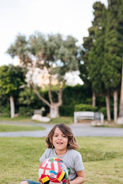 Kind spelen met een voetbal Gratis Foto