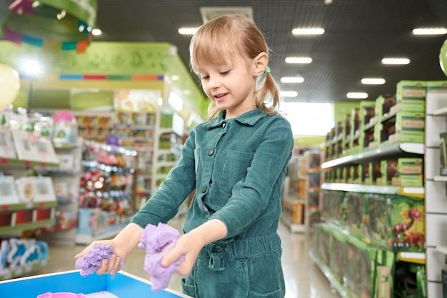 Kind spelen met kinetisch zand in speelkamer van winkel. Gratis Foto