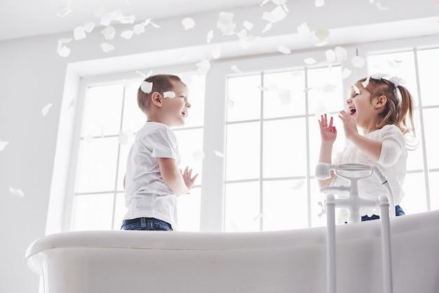 Kind spelen met rozenblaadjes in huis badkamer. klein meisje en jongen fawing plezier en vreugde samen. kindertijd en de realisatie van dromen, fantasie, verbeelding Premium Foto