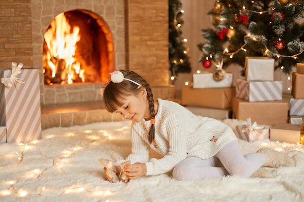 Kind spelen met speelgoed op kerstochtend Premium Foto