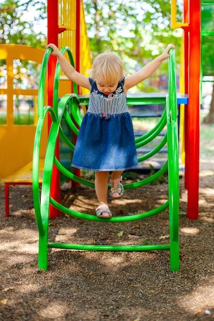 Kind spelen op buitenspeeltuin. kleine baby meisje speelt op school of kleuterschool werf Premium Foto