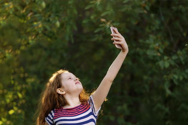 Kind stak zijn hand op met smartphone en vangt een signaal of wi-fi op. Premium Foto