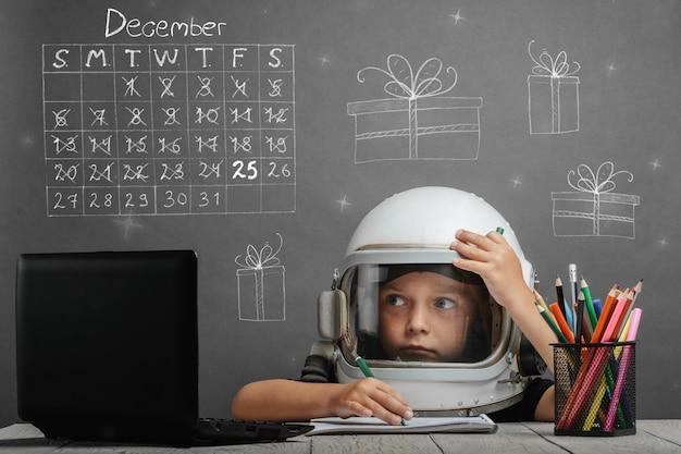 Kind studeert op afstand op school, met een astronautenhelm op. kerst concept Premium Foto