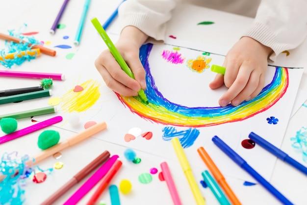 Kind tekent een regenboog met markeringen Premium Foto