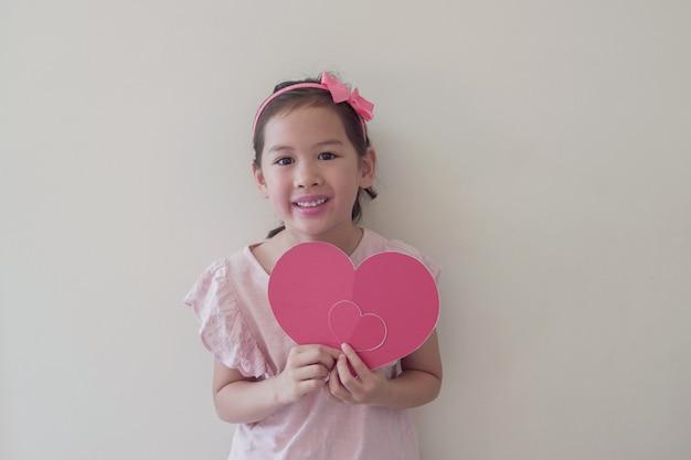 Kind van gemengd ras met een groot rood hart, hartgezondheid, donatie, gelukkige vrijwilligersliefdadigheid, sociale verantwoordelijkheid, wereldhartdag, wereldgezondheidsdag, werelddag voor geestelijke gezondheid, welzijn, hoopconcept Premium Foto