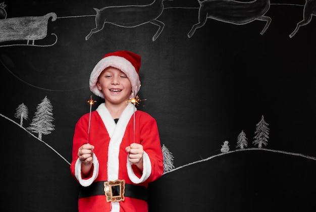 Kind verkleed als kerstman genieten van een sterretje Gratis Foto
