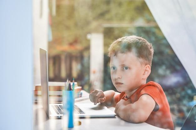 Kind wordt afgeleid van zijn studie en kijkt uit het raam Premium Foto