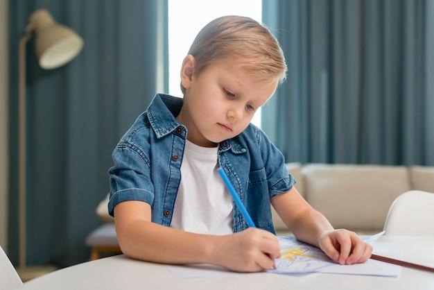 Kind zit thuis aan de tafel en schrijft Gratis Foto