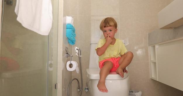 Kind zittend toilet met doordachte look pakt zijn neus Premium Foto