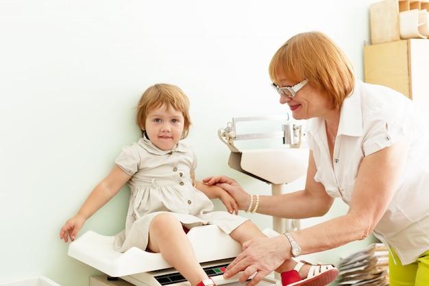 Kinderarts die de baby weegt Gratis Foto