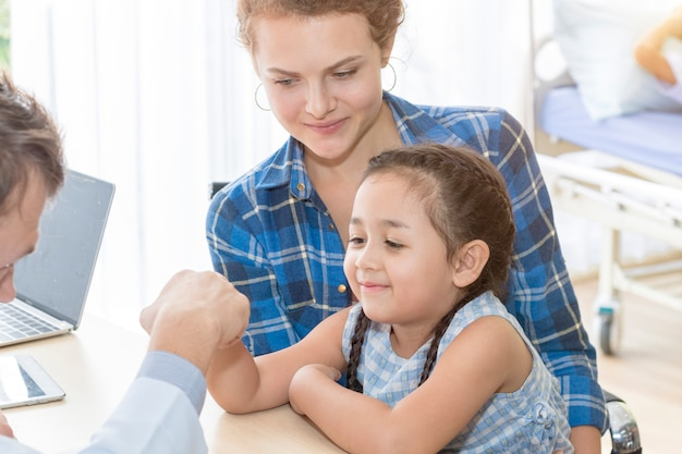 Kinderarts man die vuist hobbel geeft (high five to), geruststellend en bespreken kind op een operatie. Premium Foto