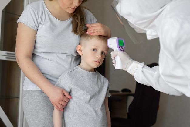 Kinderarts of arts controleert lichaamstemperatuur van elementaire leeftijd jongen met infrarood voorhoofdthermometer voor virussymptoom - concept van epidemische coronavirusuitbraak Premium Foto