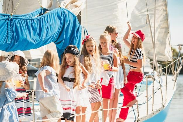 Kinderen aan boord van een zeejacht die sinaasappelsap drinken. tiener of kindmeisjes tegen blauwe hemel buiten Gratis Foto