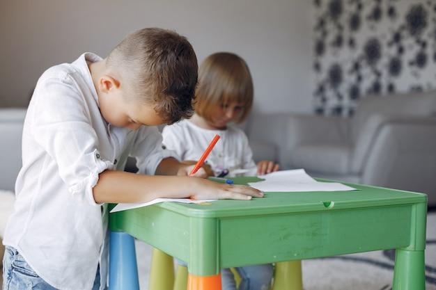 Kinderen aan de groene tafel en tekenen Gratis Foto