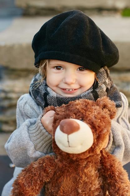 Kinderen baby in retro herfst lente kleding. klein kind zit glimlachend in de natuur, sjaal om zijn nek, koel weer. heldere emoties op zijn gezicht. , Premium Foto