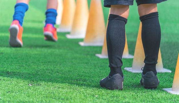 Kinderen bij voetbal opleiding op groen openluchtvoetbalgebied Premium Foto