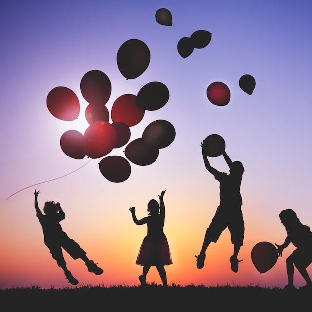 Kinderen buiten spelen met ballonnen Premium Foto