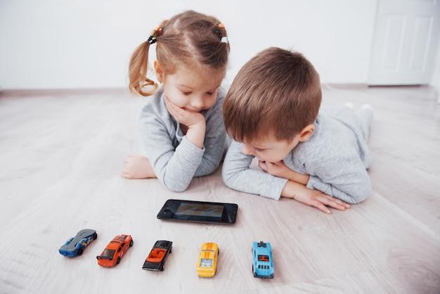 Kinderen die digitale gadgets thuis gebruiken. broer en zus op pyjama kijken naar tekenfilms en spelen games op hun technologietablet Premium Foto