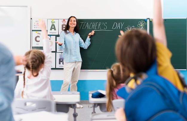 Kinderen die een vraag van hun leraar willen beantwoorden Gratis Foto