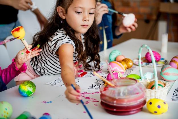 Kinderen die het schilderen eieren pasen vakantie kleuren foto