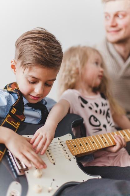 Kinderen die hun vadergitaar aanraken Gratis Foto