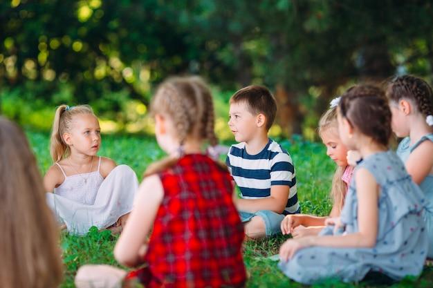 Kinderen en onderwijs, jonge vrouw op het werk als boek van de opvoedingslezing aan jongens en meisjes in park. Premium Foto