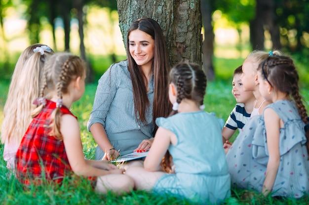 Kinderen en onderwijs, jonge vrouw op het werk als opvoeder leesboek voor jongens en meisjes in het park Premium Foto