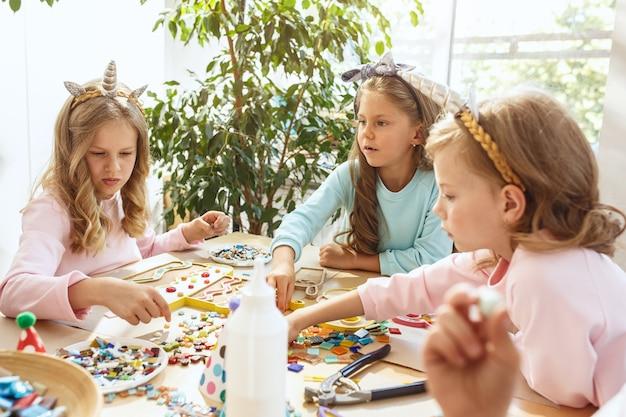 Kinderen en verjaardagsdecoratie. jongens en meisjes aan tafel met eten, gebak, drankjes en feestgadgets. Gratis Foto