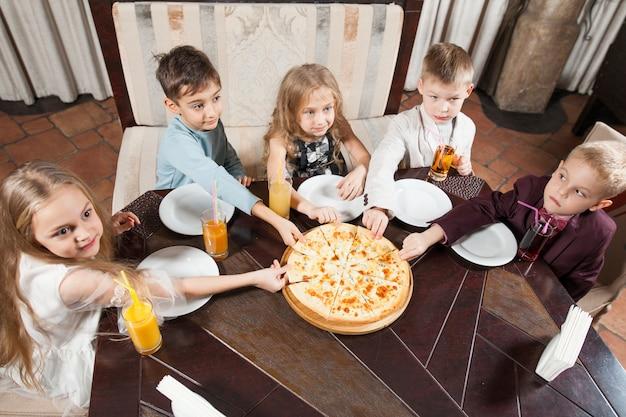 Kinderen eten pizza in een restaurant. Premium Foto