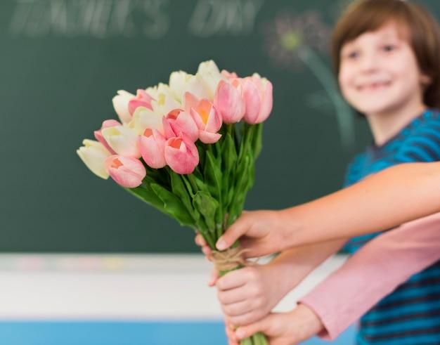 Kinderen geven bloemen met kopie ruimte Premium Foto