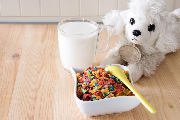 Kinderen gezond snel ontbijt. kleurrijk rijstgraangewas, melk en hondstuk speelgoed op houten achtergrond. ruimte kopiëren Premium Foto
