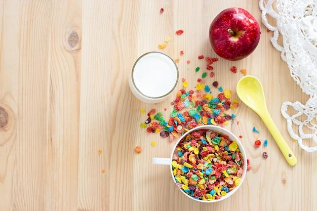 Kinderen gezond snel ontbijt. kleurrijk rijstgraangewas, melk en rode appel voor jonge geitjes op houten achtergrond. ruimte kopiëren Premium Foto
