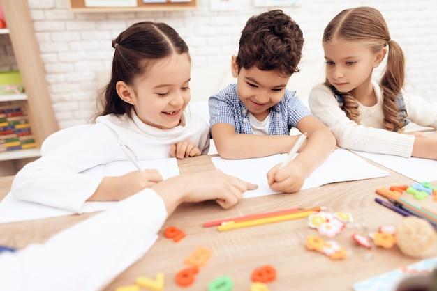 Kinderen glimlachen en schrijven in notitieboekjes met een pen. Premium Foto