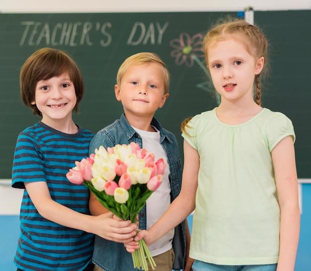 Kinderen houden een boeket bloemen voor hun leraar Gratis Foto