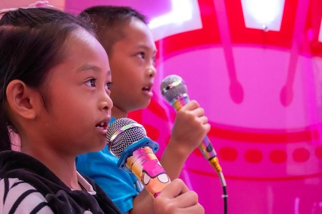 Kinderen houden van een microfoon zingen in de kamer met neonlichten. Premium Foto