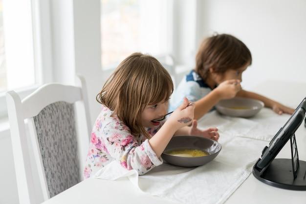 Kinderen in de eetkamer eten en kijken naar de tablet Premium Foto