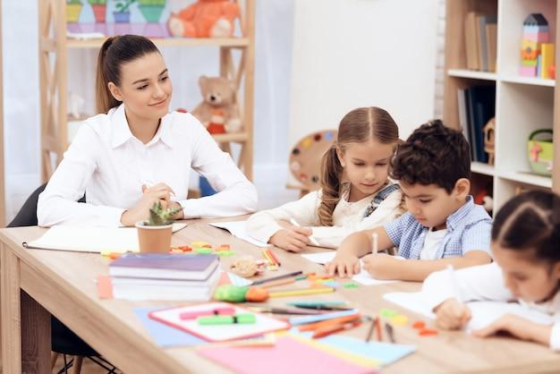 Kinderen in de kleuterschool leren tekenen met potloden. Premium Foto