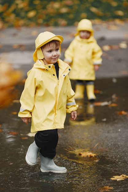 Kinderen in een herfstpark. kinderen in gele regenjassen. mensen hebben plezier buitenshuis. Gratis Foto