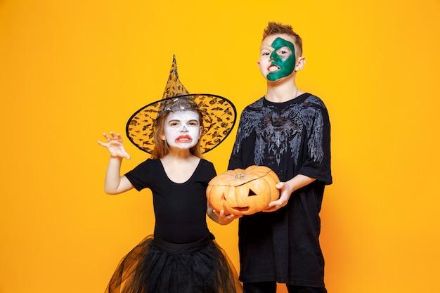 Kinderen in halloween-kostuums die een pompoen houden Premium Foto
