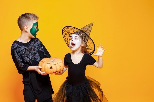 Kinderen in halloween-kostuums spelen met pompoen Premium Foto